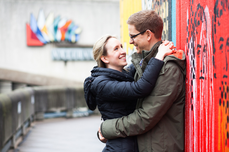 Couple hugging next to colourful wall.