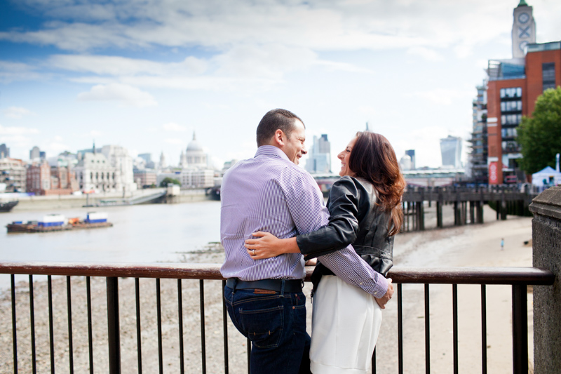 Man and lady arm in arm in front of St Paul's Cathedral and the Oxo Tower.