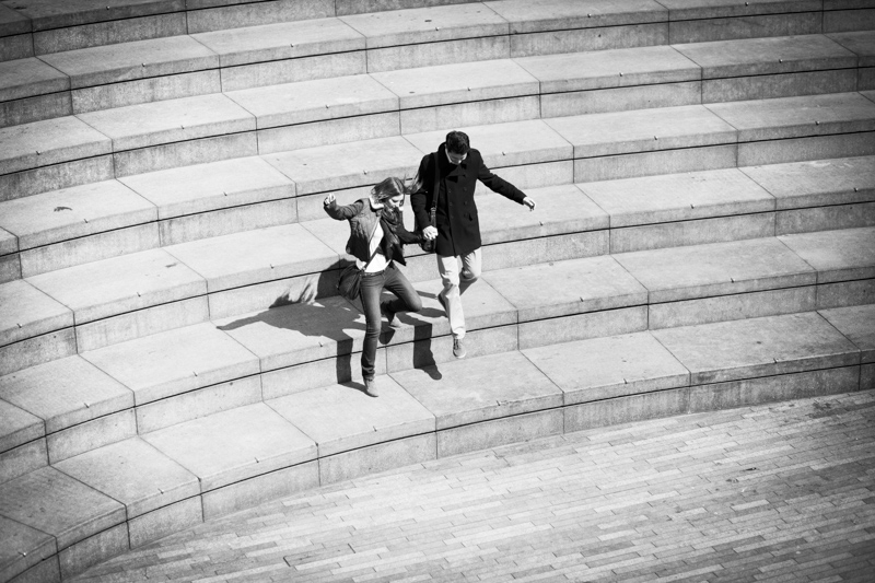 Couple jumping down stairs.
