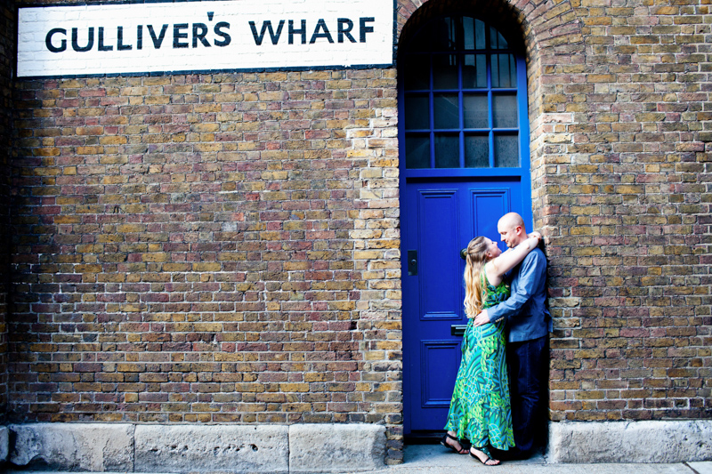 Couple hugging in front of blue door with Gulliver's Wharf sign on wall.