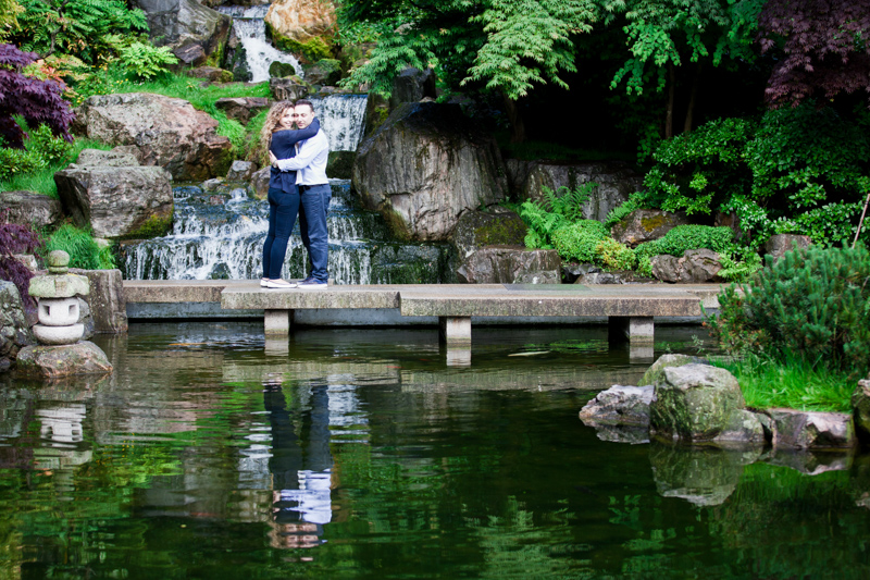 Couple hugging with waterfall behind them and pond in front of them.