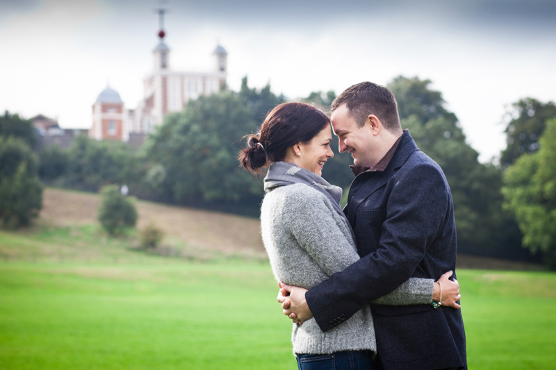 Couple looking at each other with their heads touching and Royal Observatory in the background.