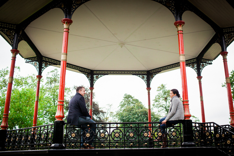 Couple sitting in a bandstand looking at each other.
