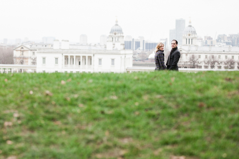 Couple with grass in the foreground and the Royal Naval College in the background.