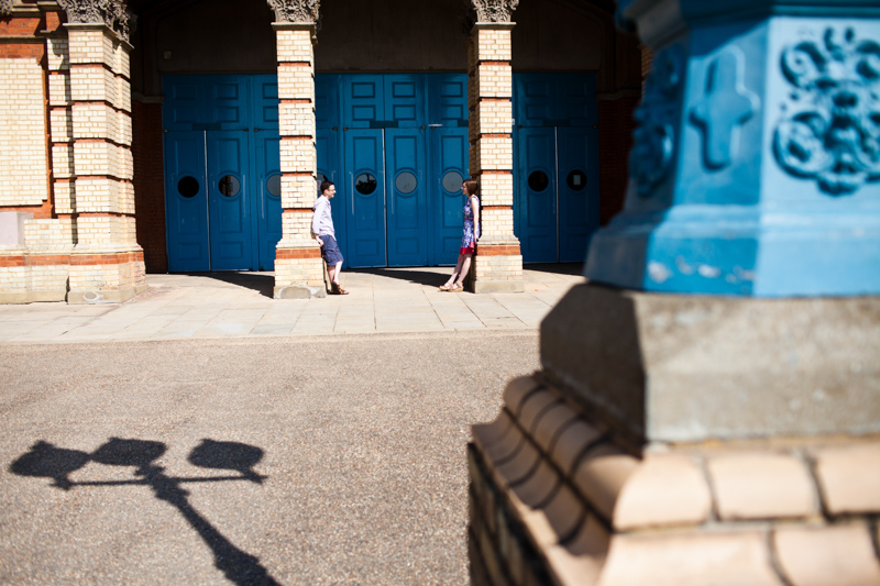 Couple leaning on pillars looking at each other in front of blue doors.