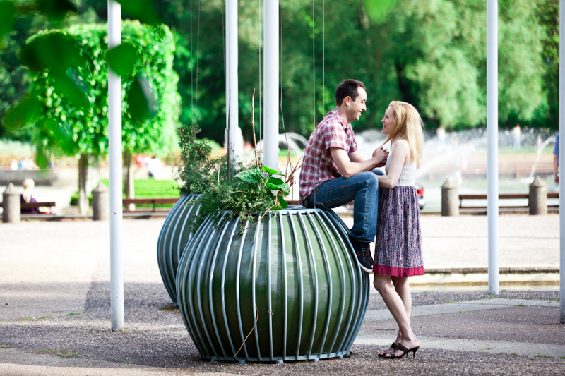 Man sitting on large plant pot looking at lady.