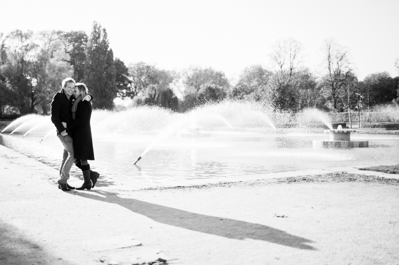 Couple hugging in front of fountain.