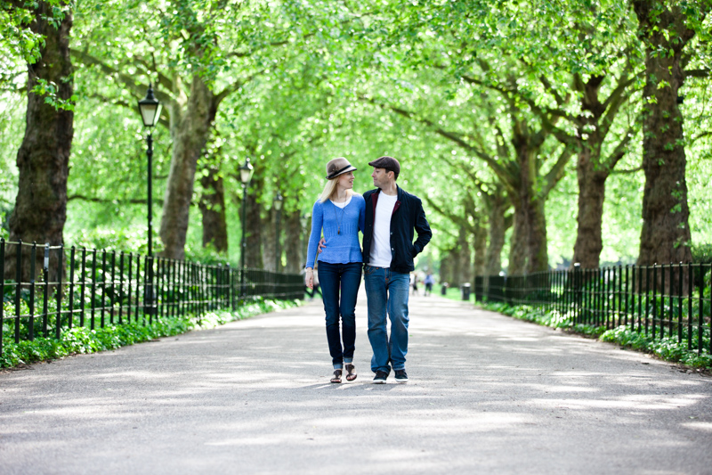 Couple walking arm in arm though avenue of trees.
