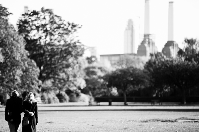 Couple walking across park with Battersea Power Station in the background.