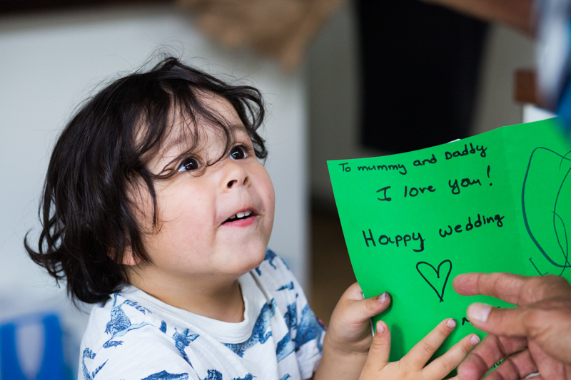 "Little boy holding green card saying ""Happy Wedding Day"""