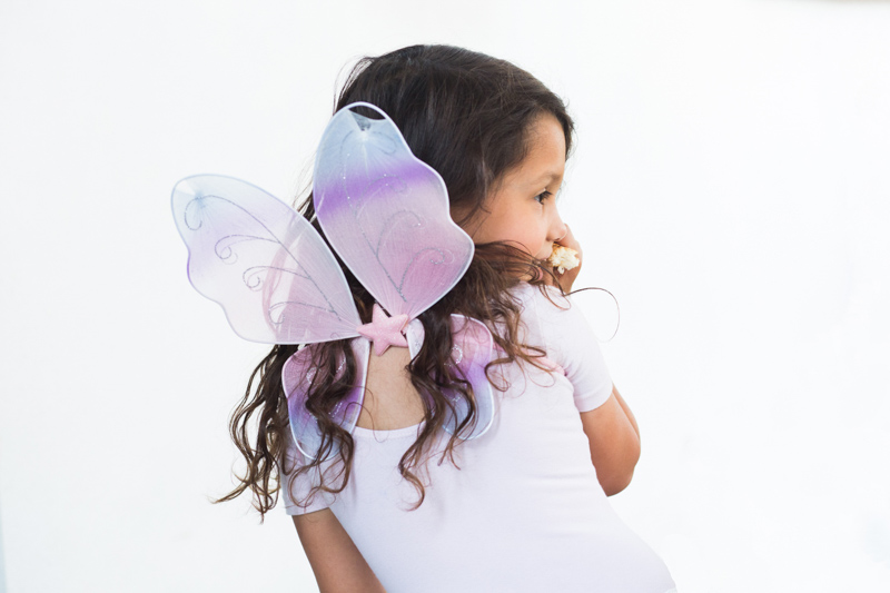 Little girl with pink wings on her back.