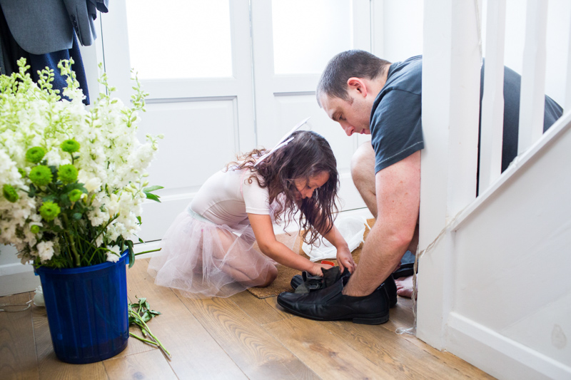 Little girl helping man polish his shoes.