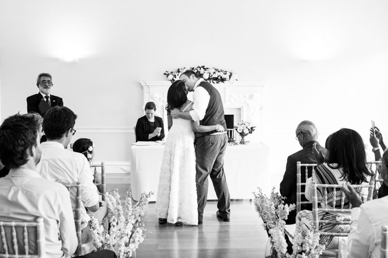 Bride and groom kissing at wedding ceremony.