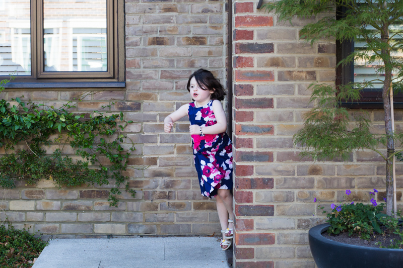 Little girl in flowery dress falling out of a doorway.