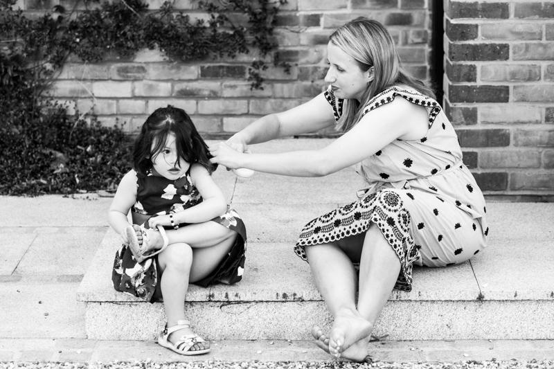 Lady brushing little girl's hair