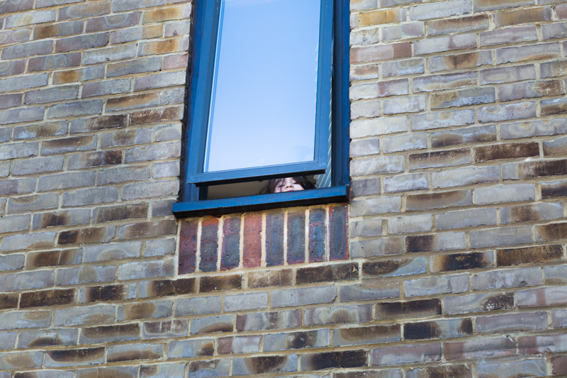 Girl looking out of upstairs window.