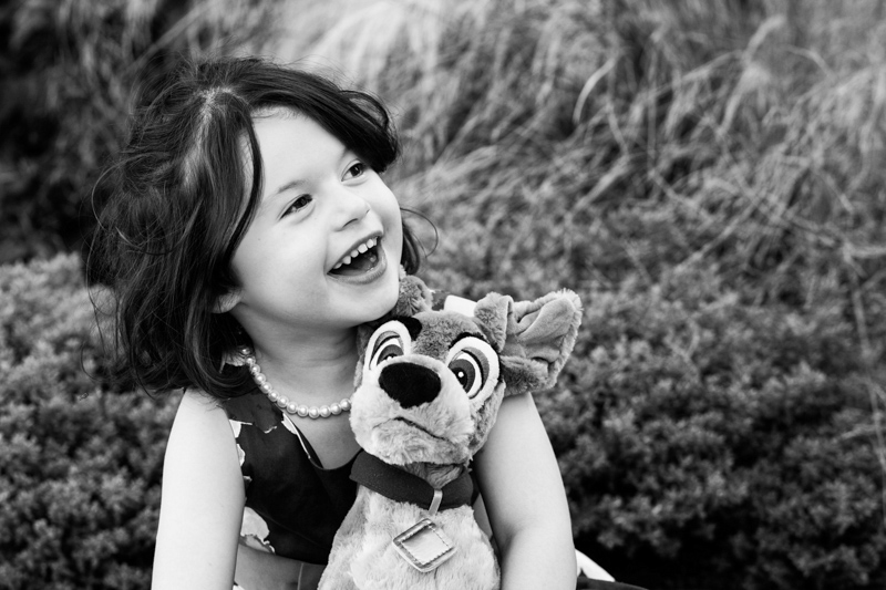 Girl laughing and holding her cuddly toy.