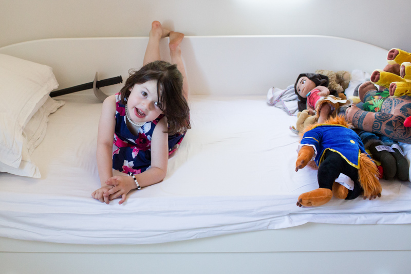 Little girl lying on her bed with her toys.