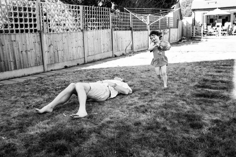 Girl running on grass around man lying on grass.