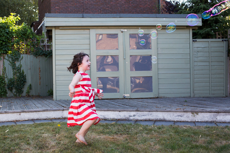 Girl chasing bubbles in front of green shed.