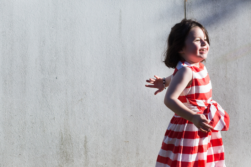 Girl in stripey dress in front of white wall with her face in the sun.