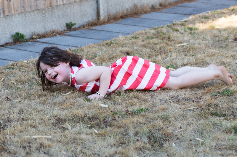 Girl in red and white stripey dress lying on the grass.