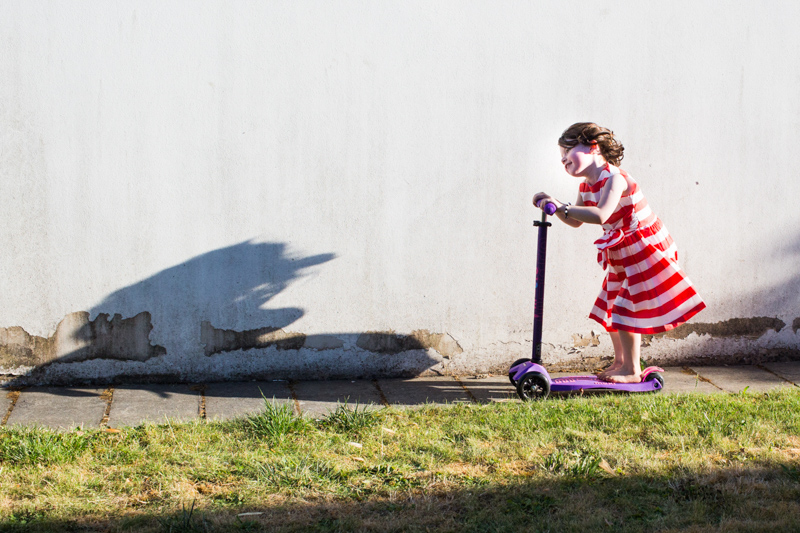 Little girl scooting in front of white wall towards her shadow