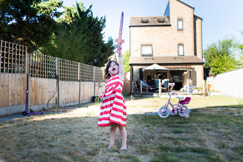 Girl in red and white dress holding toy sword up in front of house.
