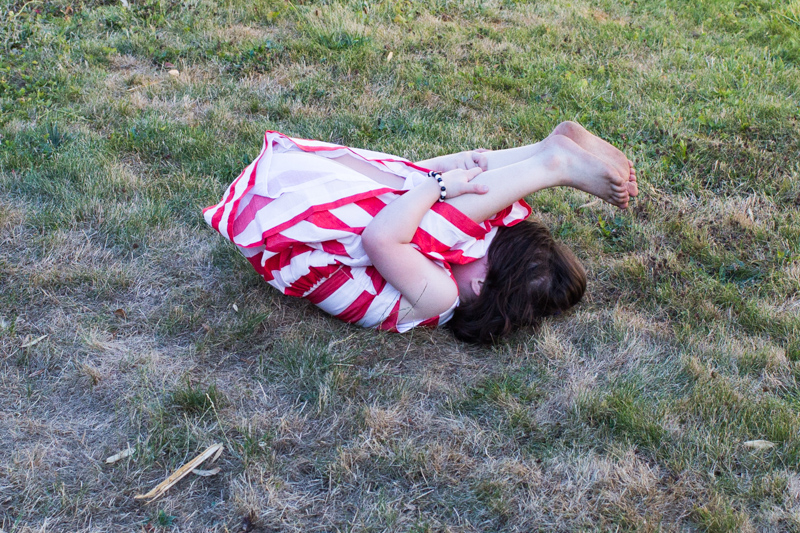 Girl lying on the grass holding onto her legs.
