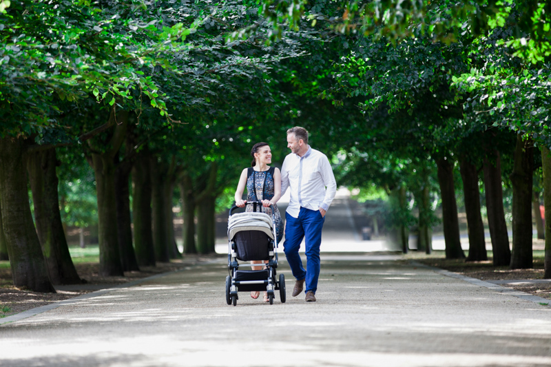 Mum and dad pushing a pram through an avenue of trees.