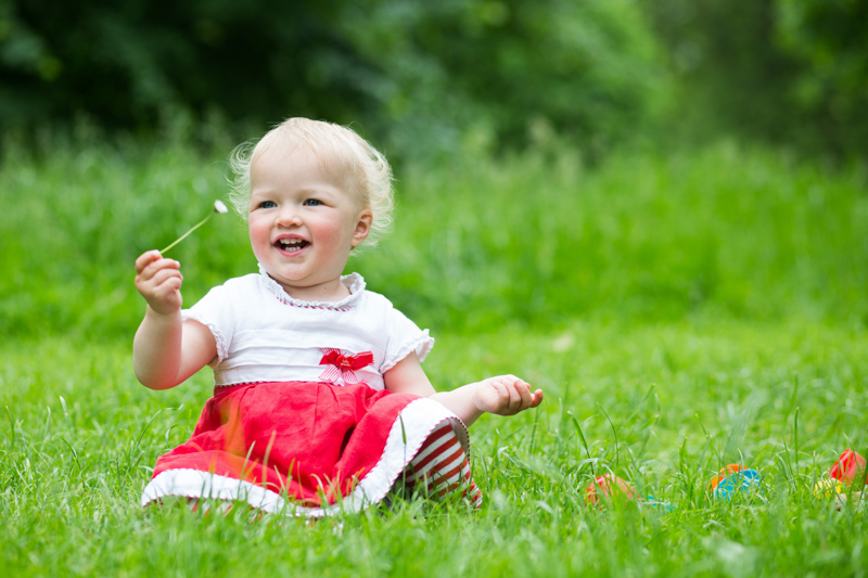 Baby girl in red and white dress sitting on the grass holding a daisy.