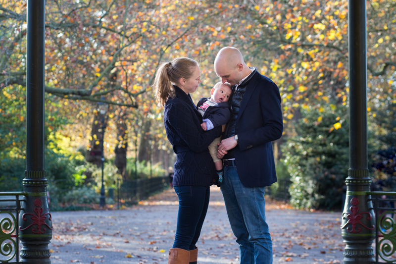 Man and lady holding their baby with autumn leaves in the background.