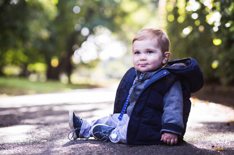 Baby in blue jacket sitting on path with trees in the background.