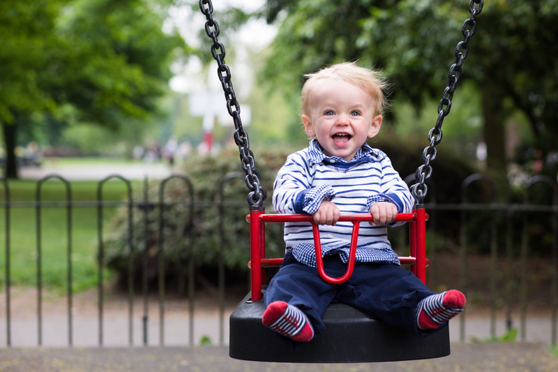 Baby boy in a stripey top laughing in a red swing.