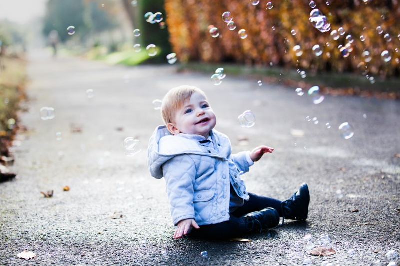 Baby sitting on path surrounded by bubbles.