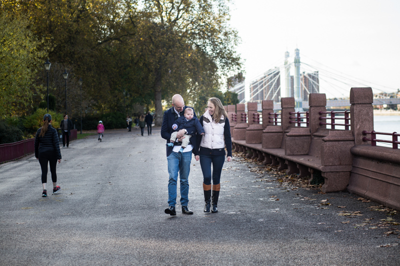 Parents carrying baby and walking by River Thames with Albert Bridge in the background.