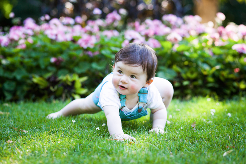 Little baby girl crawling on grass with pink flowers behind.