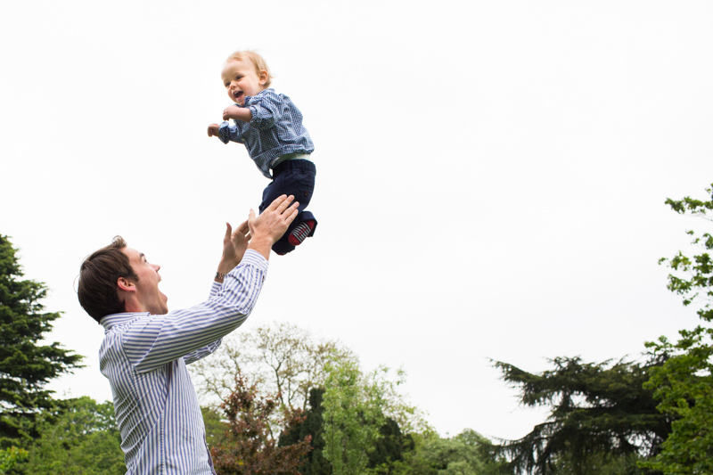 Baby boy being thrown in the air by his daddy.