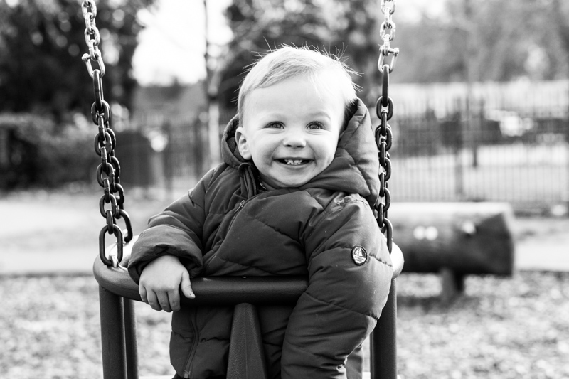 Very smiley baby in swing in park