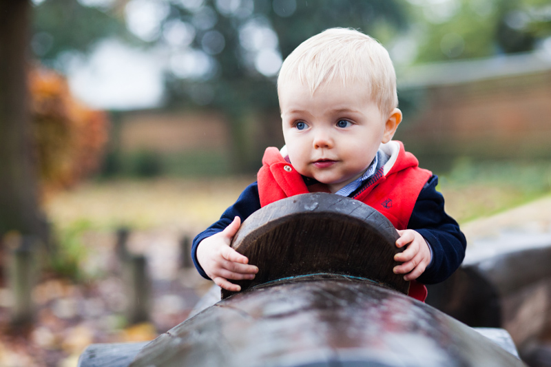 Baby boy driving a wooding car in the park.