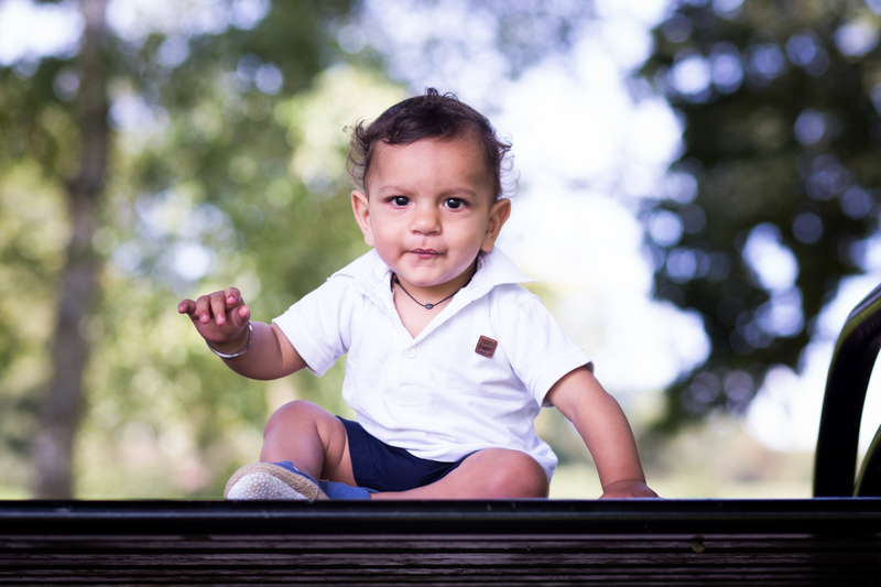 Baby boy sitting on bench smiling at camera.