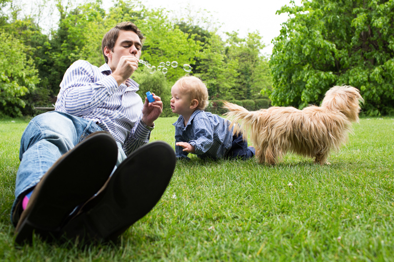 Man lying on grass blowing bubbles with baby boy and dog next to him.