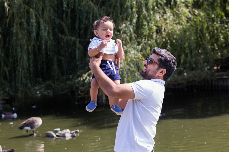 Father holding up his laughing baby boy in front of duck pond.