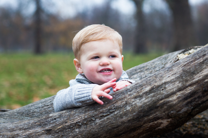 Smiling baby standing leaning on large tree trunk.