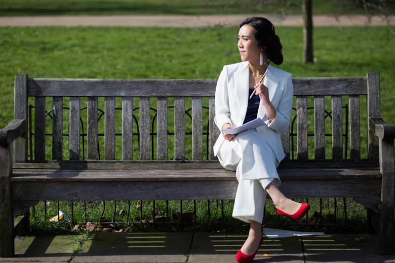 Lady in white suit and red shoes, sitting on a bench holding a pencil and music.
