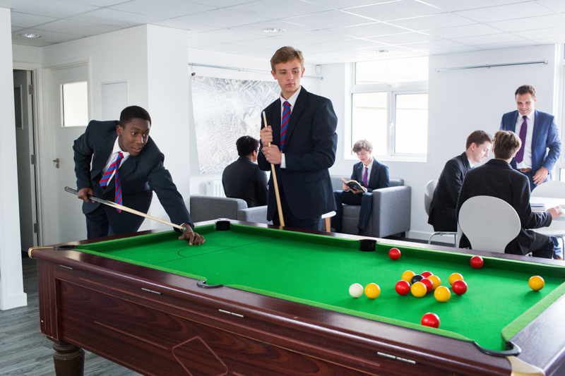 Two schoolboys playing snooker with other people behind them.
