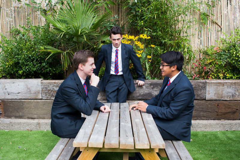 Two schoolboys sitting at a wooden table and one schoolboy behind them in front of the flowers.