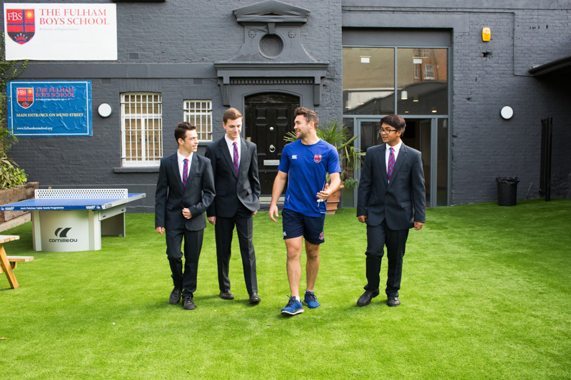 "The boys and a gym teacher walking across the grass with ""The Fulham Boys School"" in the background."