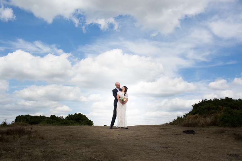 Wedding couple looking at each other on top of a hill with blue sky and white clouds behind them.