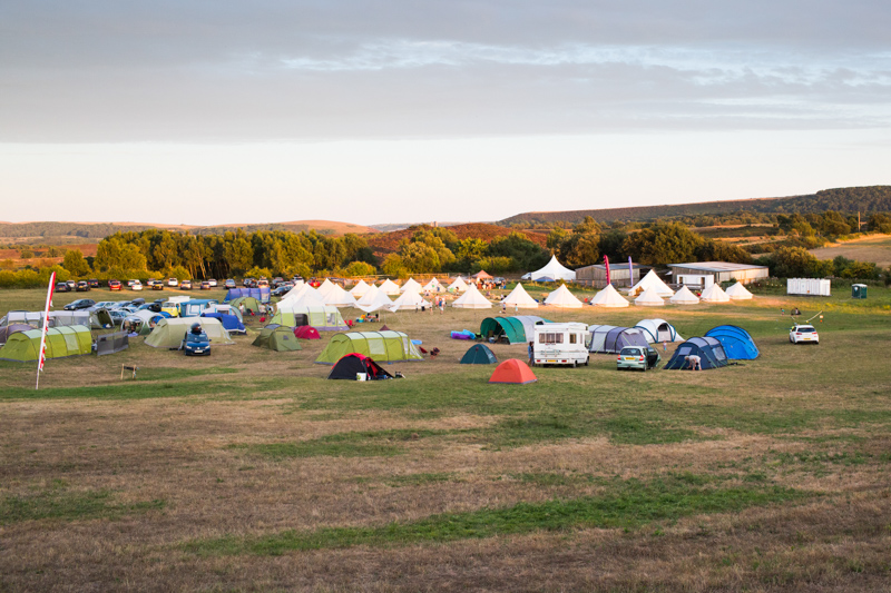 Lots of tents and glamping tents in the countryside.